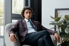 portrait d'homme d'affaires sûr dans le costume se reposant dans le fauteuil et regardant l'appareil-photo Photographie stock