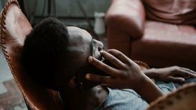 Portrait d'homme africain se reposant dans la chaise dans une salle lumineuse et parlant sur Smartphone Homme riant et ayant l'am Photos libres de droits
