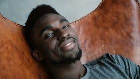 Portrait d'homme africain se reposant dans la chaise, souriant et regardant directement l'appareil-photo Le mâle semble rêveur, r clips vidéos