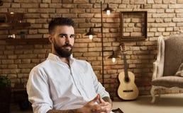 Portrait d'homme barbu à la maison de grenier avec la guitare photo stock