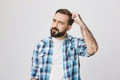 Portrait d'homme barbu européen avec des émotions perplexes, scretching sa tête, exprimant qu'il est naïf, au-dessus du gris Photographie stock libre de droits