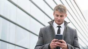 Portrait d'homme bel d'affaires utilisant le smartphone et le boire photographie stock libre de droits