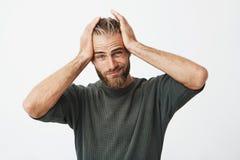Portrait d'homme bel avec la coiffure élégante et la barbe ayant fatigué l'expression en raison du mal de tête après dure journée images stock