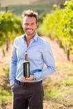 Portrait d'homme bel tenant la bouteille de vin Photos stock