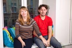 Portrait d'homme caucasien et de femme s'asseyant sur le filon-couche de fenêtre ensemble Photographie stock