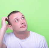 Portrait d'homme confus sur le fond vert recherchant Image stock