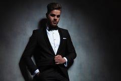 Portrait d'homme décontracté déboutonnant son costume de noir de smoking Images libres de droits