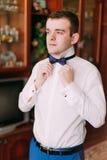 Portrait d'homme d'affaires bel dans le costume bleu mettant sur le noeud papillon à l'intérieur Photographie stock libre de droits