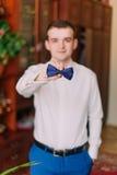 Portrait d'homme d'affaires bel dans le costume bleu mettant sur le noeud papillon à l'intérieur Photos stock