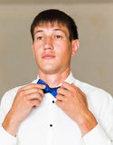 Portrait d'homme d'affaires bel dans le costume mettant sur le noeud papillon à l'intérieur Images libres de droits