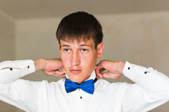Portrait d'homme d'affaires bel dans le costume mettant sur le noeud papillon à l'intérieur image libre de droits