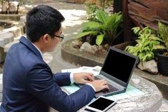 Portrait d'homme d'affaires bel travaillant avec l'ordinateur portable dehors en parc de ville Photographie stock