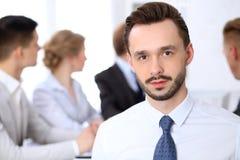 Portrait d'homme d'affaires contre un groupe de gens d'affaires lors d'une réunion Photographie stock libre de droits