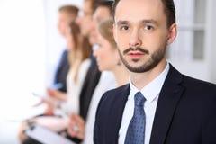 Portrait d'homme d'affaires contre un groupe de gens d'affaires lors d'une réunion Images libres de droits