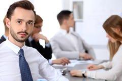 Portrait d'homme d'affaires contre un groupe de gens d'affaires lors d'une réunion Image stock