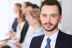 Portrait d'homme d'affaires contre un groupe de gens d'affaires lors d'une réunion Images stock