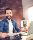 Portrait d'homme d'affaires de sourire utilisant le comprimé graphique et l'ordinateur portable Image stock