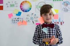 Portrait d'homme d'affaires mignon avec les notes collantes se tenant contre le tableau blanc dans le bureau image stock