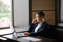 Portrait d'homme d'affaires parlant sur son smartphone en café Photo stock
