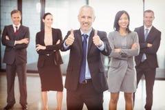 Portrait d'homme d'affaires renonçant à des pouces et à des gens d'affaires se tenant avec des bras croisés Image libre de droits