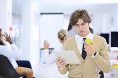 Portrait d'homme d'affaires sûr utilisant le comprimé numérique tandis que collègue à l'arrière-plan photographie stock libre de droits