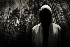 Portrait d'homme dangereux sous le capot dans la forêt photo stock