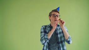 Portrait d'homme de joyeux anniversaire dans le klaxon de soufflement et rire de partie de chapeau lumineux banque de vidéos