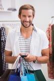 Portrait d'homme de sourire avec des paniers utilisant le smartphone Photographie stock