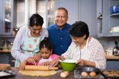 Portrait d'homme de sourire avec la famille préparant la nourriture dans la cuisine photo libre de droits