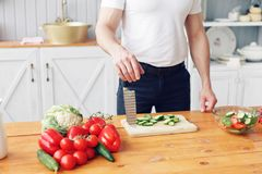 Portrait d'homme de sourire bel à la cuisine cuisson et concept à la maison - fermez-vous de la main masculine coupant le concomb photo stock