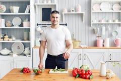 Portrait d'homme de sourire bel à la cuisine cuisson et concept à la maison - fermez-vous de la main masculine coupant le concomb photographie stock