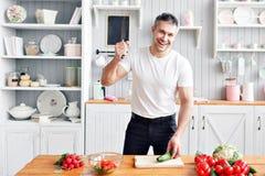 Portrait d'homme de sourire bel à la cuisine cuisson et concept à la maison - fermez-vous de la main masculine coupant le concomb photos libres de droits