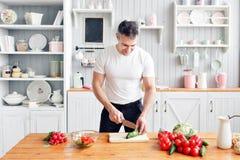 Portrait d'homme de sourire bel à la cuisine cuisson et concept à la maison - fermez-vous de la main masculine coupant le concomb photographie stock libre de droits