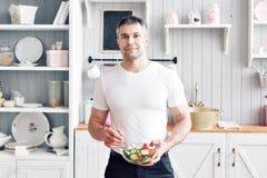 Portrait d'homme de sourire bel à la cuisine cuisson et concept à la maison - fermez-vous de la main masculine coupant le concomb image libre de droits
