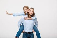 Portrait d'homme de sourire donnant à femme heureuse un tour de ferroutage Images libres de droits