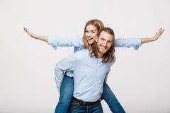 Portrait d'homme de sourire donnant à femme heureuse un tour de ferroutage Images stock