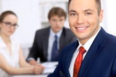 Portrait d'homme de sourire gai d'affaires contre un groupe de gens d'affaires lors d'une réunion Image stock