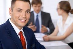 Portrait d'homme de sourire gai d'affaires contre un groupe de gens d'affaires lors d'une réunion Photographie stock