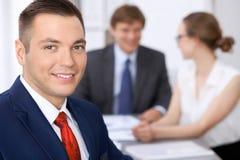 Portrait d'homme de sourire gai d'affaires contre un groupe de gens d'affaires lors d'une réunion Image libre de droits