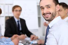 Portrait d'homme de sourire gai d'affaires contre un groupe de gens d'affaires lors d'une réunion Photos stock