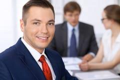 Portrait d'homme de sourire gai d'affaires contre un groupe de gens d'affaires lors d'une réunion Photo stock