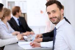 Portrait d'homme de sourire gai d'affaires contre un groupe de gens d'affaires lors d'une réunion Photo libre de droits