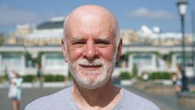 Portrait d'homme de sourire se tenant dehors regardant l'appareil-photo Retraité voyageant à Moscou, Russie banque de vidéos