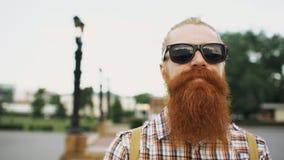 Portrait d'homme de touristes barbu de hippie dans des lunettes de soleil regardant l'appareil-photo et souriant au fond de ville photos libres de droits