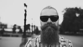 Portrait d'homme de touristes barbu de hippie dans des lunettes de soleil regardant l'appareil-photo et souriant au fond de ville images libres de droits
