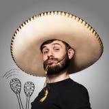 Portrait d'homme drôle dans le sombrero mexicain sur le fond gris Photos stock