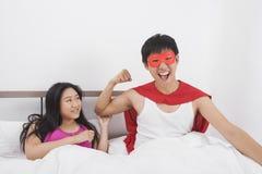Portrait d'homme enthousiaste dans le costume de super héros avec la femme sur le lit Photographie stock libre de droits