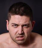 Portrait d'homme fâché sur le fond foncé Image stock