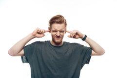Portrait d'homme frustrant tenant des doigts dans des oreilles photographie stock