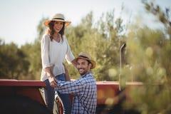 Portrait d'homme heureux tenant l'amie se tenant sur le tracteur Image stock